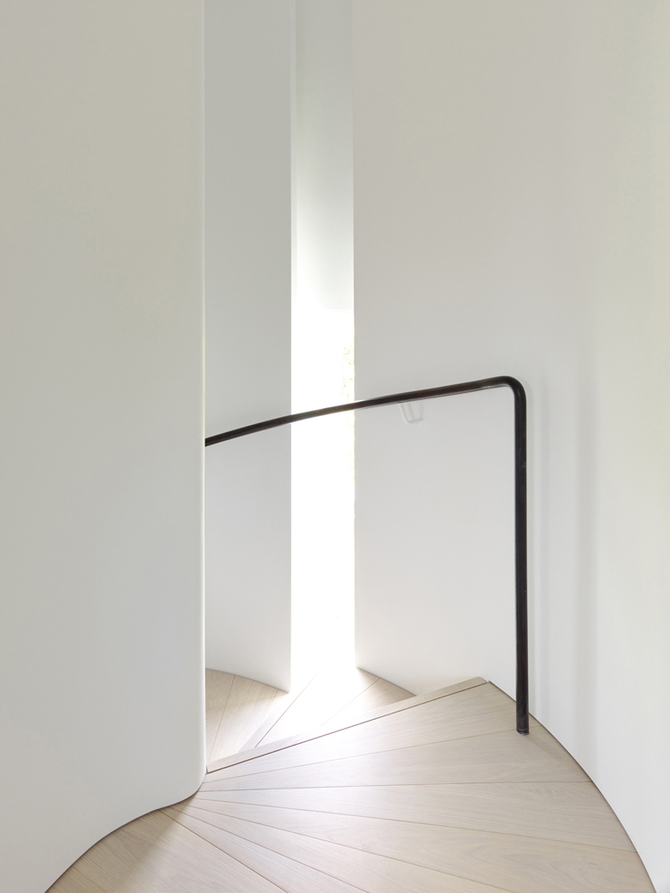 Curved Stair and Light with Black Handrail